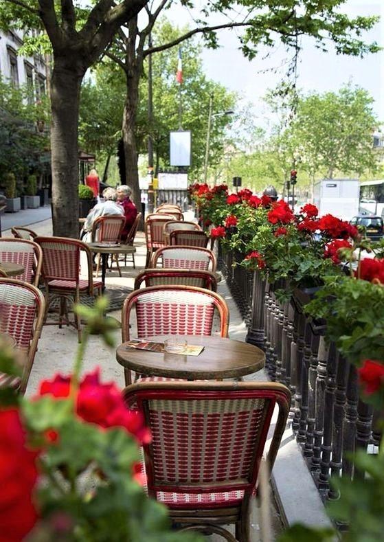 ristorantino francese con tavolini rotondi e fiori rossi