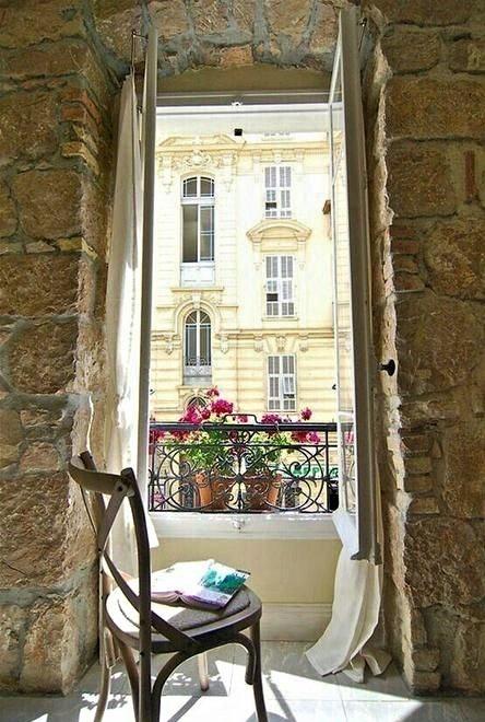 sedia in legno su balcone con fiori