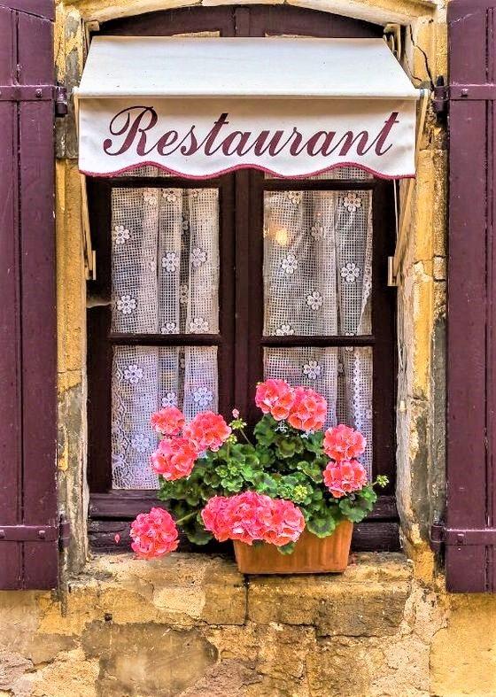 finestra di un ristorante parigino con fiori fuxia